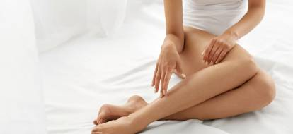 woman sitting on the bed with white covers touching her legs